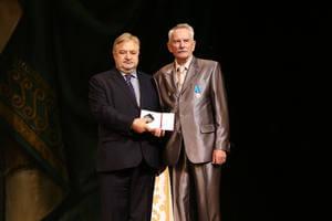 Пётр Костенич награждает нагрудным знаком Германа Русанова